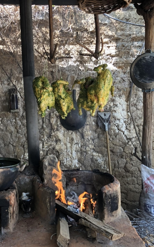 Chicken hung over a hearth that smokes for a couple hours.